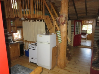 Kitchen, bedroom (behind curtain) and loft above.